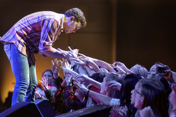 "Scotty McCreery writes on hands during a performance of ""Write My Number on Your Hand"" Sunday night during Jingle Bell Jam in York. (Bil Bowden Photo)"